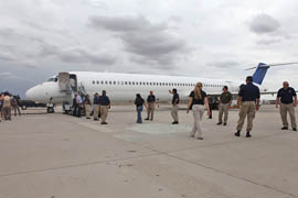 Immigration and Customs Enforcement officials board a plane in Tucson that is headed for Mexico City under the agency's immigrant repatriation flights program in this 2011 file photo.