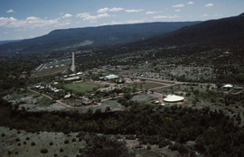 Aerial view of district of the Fort Apache site, looking east, with canyon of East Fork of White River in foreground, and the white cone roof of Nohwike' Bagowa Museum on right center.
