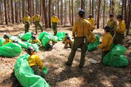 Phillip Maldonado, a squad leader with the Granite Mountain Hotshots, helps crew member learn the finer points of setting up emergency fire shelters. Training is key as the crew prepares for what's expected to be a busy wildfire season.