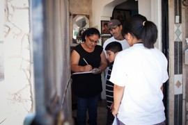 Mi Familia Vota volunteer Yvette Saenz, 19, registers Guadalupe and Manuel Mercado for the permanent early voter list as their grandson, Alex Mercado, watches. Saenz also registered two other family members in the house.