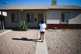 Mi Familia Vota volunteer Yvette Saenz approaches one of the last houses during her visit to a west Phoenix neighborhood. On a good day Marissa Galindo said she can register 12 to 15 people for the permanent early voter list.