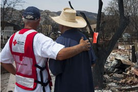American Red Cross volunteer Marty Martindale provides some encouragement to Yarnell resident Gene Criner, one of scores who lost homes in the wildfire that killed 19 Granite Mountain Hotshot firefighters on June 30.