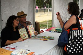 Monica Brown, left, and Rafael López, right, pose while Geri Ramos Morton takes a photo of them at the National Book Festival, Saturday in Washington, D.C.
