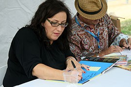 Monica Brown, left, and Rafael López sign copies of their books for fans at the National Book Festival, Saturday in Washington, D.C.