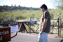 Terry Labansat, visiting from Fort Worth, Texas, arrives at Montezuma Castle National Monument to find a locked gate Tuesday.