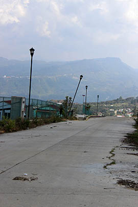Damaged light poles line an empty street in the Sustainable Rural City of Santiago el Pinar in Chiapas, Mexico.