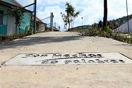 The government slogan 'Deeds, not words' is imprinted on a sidewalk in front of an abandonded houses in the Sustainable Rural City of Santiago el Pinar in Chiapas, Mexico.