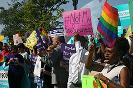 Hundreds of pro-choice protesters, countered by hundreds of pro-life demonstrators, rallied outside the Supreme Court before it ruled in the Hobby Lobby case.