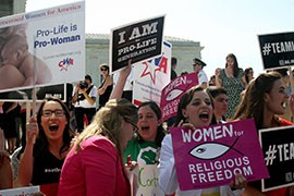 Pro-life protesters celebrate outside the Supreme Court after it ruled that business owners cannot be forced to provide certain contraceptive coverage to employees if it conflicts with their religious convictions.