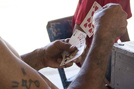 Men waiting to head north pass the time at the House of Mercy playing cards.