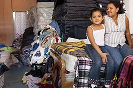 Meybol del Rosario Rugama Urbina and her 6-year-old daughter, Paola, sit on a bed in the House of Mercy's women's quarters, where shelter operators stack donated clothes and extra mattresses.