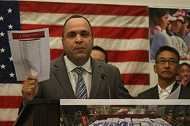 Jose Calderon, the president of the Hispanic Federation, holds up a copy of the 2014 National Immigration Score Card that was produced by his and other immigrant advocacy organizations.