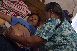 Dona Mercedes, a traditional midwife, checks on Maria Lopez Mendoza, then six months pregnant, shortly before she declared Lopez's baby