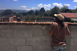 Claudia Vasquez Perez looks out at the farm and San Cristóbal beyond from the rooftop at K'inal Antzetik women's cooperative.