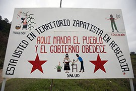 The sign at the gate to Caracol Morelia depicts the Zapatista lifestyle - production and agriculture, health and education. Visitors to the caracoles, the independent Zapatista communities, need to be approved by the Council of Good Governance before entry.