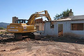 A backhoe demolishes a building on the Navajo Nation that was contaminated by radiation exposure from abandoned uranium mines. The EPA reported that during the five-year plan it demolished 38 buildings because they were contaminated.