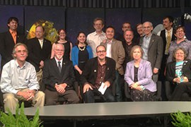 David Grinspoon, center, and other panelists, front row, who met to talk about the space probe New Horizons, which reached Neptune this week and will reach Pluto next summer. The panelists, and the scientists and students behind them, defended Pluto's claim to planetary status.