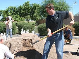 With Vice Mayor Jim Waring helping, Phoenix Mayor Greg Stanton demonstrates how to fill a sandbag Monday.