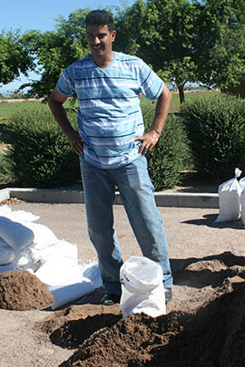 Abdullah Alkhaledy takes a break from filling sandbags, which he will use to prevent flooding around his home.