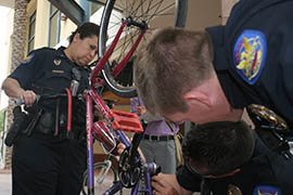 Police look over a bicycle being registered for the Back Up Your Bike Program.