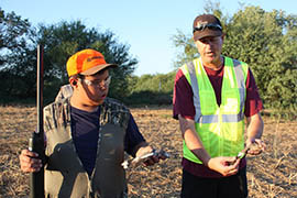 Scott Pike, an employee of Youth Outdoors Unlimited, works with 11-year-old Hunter Lopez during a hunt organized by his group.