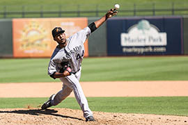 Jayson Aquino, a top prospect in the Colorado Rockies' system, delivers a pitch for the Salt River Rafters of the Arizona Fall League. The Rafters' home park in Scottsdale is testing a proposed Major League Baseball rule using a timer to get pitchers to throw faster. Six rules being tested in the Fall League are intended to speed up games.
