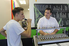 Carl Dewberry, right, co-owner of Valor Vapor in Tempe, helps a customer create a custom flavor of liquid for his e-cigarette.