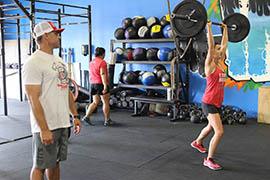 CrossFit Incite trainer Britt Burns monitors a member practicing a clean-and-jerk weight lift.