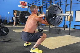 A CrossFit Incite member practices a clean weight lift.