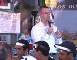 The Rev. Sean Carroll, executive director of Kino Border Initiative, prays with the migrants before dinner at the Aid Center for Deported Migrants.