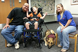 The Ludwig family (from left: Troy, Cole and Yvonne) has had Bandit, Cole's service dog, for almost a year. When Bandit barks, Cole's parents know they need to get to their son quickly. Suffering from cerebral palsy and epilepsy, Cole has silent seizures up to 10 times a week that can cause him to stop breathing.