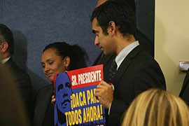 Salvador Sarmiento of the National Day Laborers' Organizing Network, one of the groups demanding executive action on immigration reform, holds a sign calling on the president to extend DACA - deferred action for childhood arrivals - to everyone.