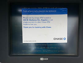 A sign on an ATM notes that one of two Chase branches in Nogales has closed.