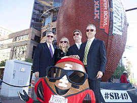 Marking the unveiling of a giant football sculpture in downtown Phoenix are, from left: Win Holden, chairman of VisitPhoenix.com; Jay Parry, president and CEO of the Arizona Super Bowl Host Committee; Phoenix Mayor Greg Stanton; and David Rousseau, chairman of the Arizona Super Bowl Host Committee. Also pictured is Spike, the Arizona Super Bowl mascot.