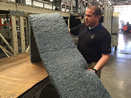 Sean Desmond, director of sales and marketing for Bonded Logic, shows the Chandler company's insulation made from old blue jeans.