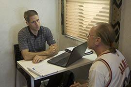 Daren Strunk, an employment outreach specialist with St. Joseph the Worker, counsels Robert Batke on job options.