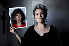 Claudia Lugo, 47, poses in her office at Crossroads Mission of Yuma with her mugshot. In 2005, Lugo turned herself in on drug sale warrants after she almost overdosed on heroin and was dumped in a ditch.