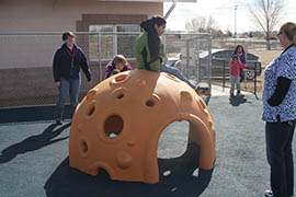The hard shell and holes on this inclusive playground structure allow students who may have difficulty grabbing bars on traditional equipment to climb on top or play inside.
