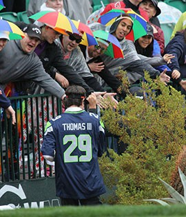 Bubba Watson hands out visors to fans while wearing the Seattle Seahawks' Earl Thomas III's jersey while walking down the fairway at the 16th hole.