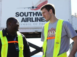 Suns head coach Jeff Hornacek, along with a group of former and current Phoenix Suns players including guard Goran Dragic (right), switched jobs with several employees of the team's official airline.