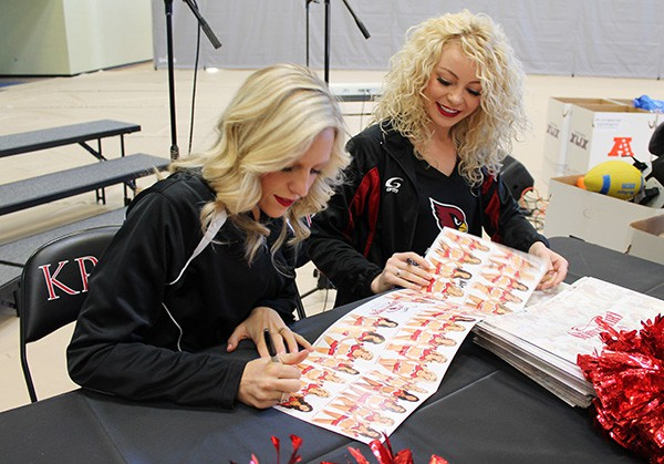 Arizona Cardinals cheerleaders Brooke (left) and Erica (right) sign autographs for students before the Kids Camp. Photo by Miranda Perez