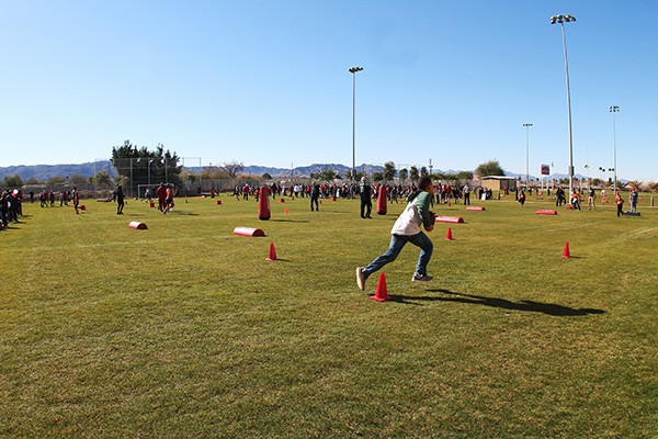 Participants run, jump, pass and catch in a rotation of drills on a sunny day outside of the Salvation Army South Mountain Kroc Community Center. Photo by Miranda Perez