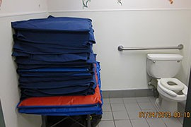 Children's sleeping mats are stored next to a toilet at one of the Arizona child-care facilities that federal inspectors audited in 2013.