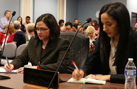 Christine Thompson and Sabrina Vazquez, the staffer's Douglas fired, take notes during the State Board of Education meeting. The panel voted to allow them back into their offices.