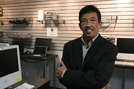 Richard Wong, president of E-Waste Harvesters, shows refurbished computers available in the Phoenix company's outlet store.