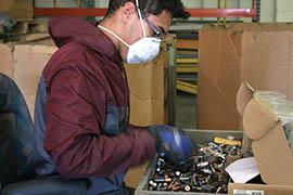 Vincent M. Villanueva sorts through batteries at E-Waste Harvesters in Phoenix.