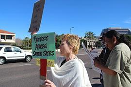 Cynthia Bittick, 57, held up signs outside of Sen. John McCain's office.