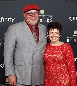 Donning one of his signature hats, Arizona Cardinals head coach Bruce Arians smiles with his wife, Christine, before winning AP Coach of the Year during the 4th Annual NFL Honors.