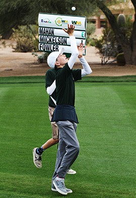 Tucker Clark, 13, throws a golf ball up in the air as his partner carries the standard