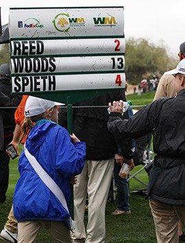 A little girl heads to the club house carrying the standard for Woods who missed the cut, finishing at 13 over.